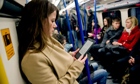 A woman reading a Kindle ebook on a London bus. Amazon says downloads have overtaken print sales